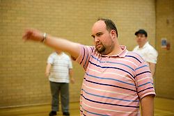 Group of Day Service users with learning disabilities doing warm up exercises in the gym,