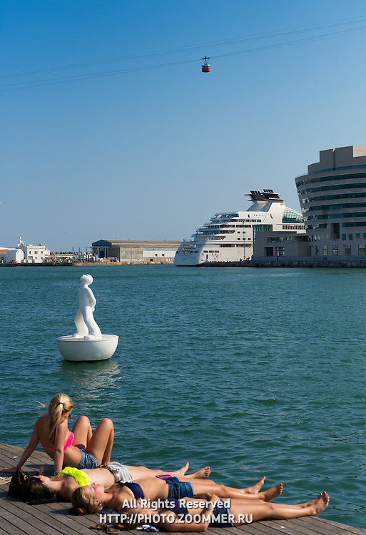 Teenager girls sunbathing in Barcelona port