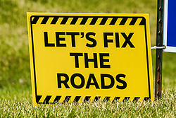 Sign along the side of a road suggesting to fix the roads