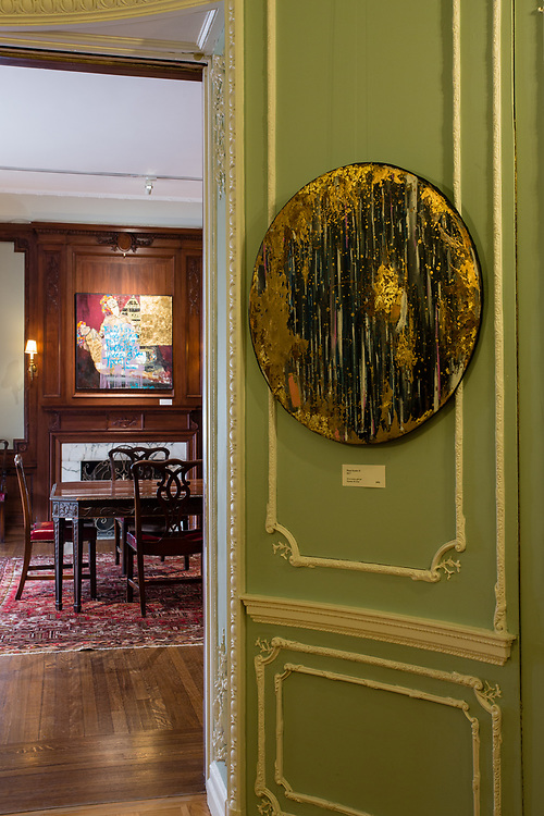 """Part of the oval sitting room in The Ukrainian Institute. The round painting is Valeriy Hnatenko's """"Planet Number II."""" Over the firplace in the next room is his """"Past."""""""