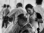 12 SEPTEMBER 2018 - BANGKOK, THAILAND: Travelers get free haircuts at Hua Lamphong train station in Bangkok. Barber schools set up in the station and offer free haircuts to travelers.     PHOTO BY JACK KURTZ