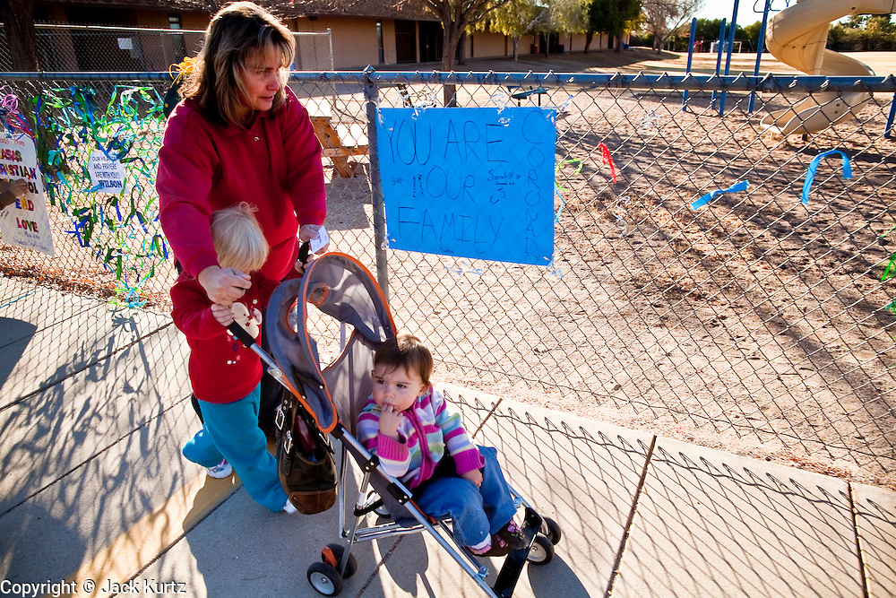 tucsonshooting - 10 JANUARY 2011 - ORO VALLEY, AZ: Denise Cook (CQ) and two of her children, Jaycee Cook (CQ) 18 months, and Nicole Cook, (CQ) 3.5 years, walk past a memorial for Christina Green Mesa Verde Elementary School in Oro Valley. Christina Green was a student at the school. Denise has a son in the school and said school counselors met with students Monday morning and told them it was okay to cry for their deceased classmate. She said the students at the school want to do something in Christina's memory.  ARIZONA REPUBLIC PHOTO BY JACK KURTZ..Gabrielle Giffords shooting
