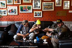 Danita Gayle drinking chai and resting her bruised leg at the end of the day on Motorcycle Sherpa's Ride to the Heavens motorcycle adventure in the Himalayas of Nepal. On the fifth day of riding, we went from Muktinath to Tatopani. Friday, November 8, 2019. Photography ©2019 Michael Lichter.