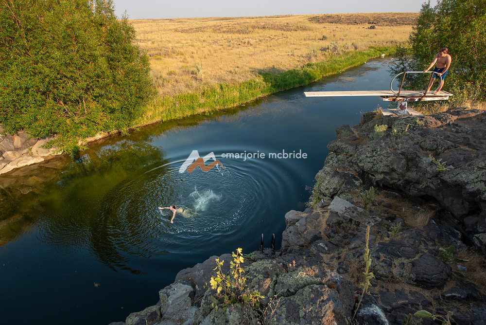 Teens jumping from the diving board at the Ledges swimming hole in Richfield, Idaho.