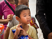 11 AUGUST 2015 - BANGKOK, THAILAND: A boy waits to make merit by giving an offering of juice drinks and potato chips to Buddhist monks during a service to honor Queen Sirikit of Thailand before her 83rd birthday. Queen Sirikit was born Mom Rajawongse Sirikit Kitiyakara on August 12, 1932. She is the queen consort of Bhumibol Adulyadej, King (Rama IX) of Thailand. She met Bhumibol in Paris, where her father was the Thai ambassador. They married in 1950, she was appointed Queen Regent in 1956. The King and Queen had one son and three daughters. She has not made any public appearances since her hospitalization in 2012. Her birthday is celebrated as Mother's Day in Thailand, schools and temples across Thailand hold ceremonies to honor the Queen and mothers.      PHOTO BY JACK KURTZ