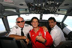 Alexandre Pato com os comandantes do avião no voo de volta para o Brasil. FOTO: Jefferson Bernardes/Preview.com