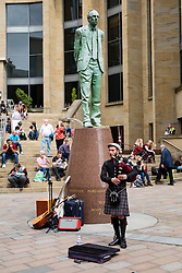 People sitting outside in the sun on steps of Glasgow Royal Concert Hall with busker playing bagpipes in Glasgow, Scotland, united Kingdom