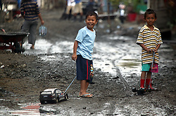 Two boys,  …………. In blue and ……………. Pull their toy cars along a street in Kampung Laksana village. Slowly being cleaned of mud and other debris. The surge, thankfully almost at the end of the Tsunami's limit damaged homes and businesses.  Oxfam has provided villagers with simple equipment such as wheel barrows, gloves and shovels to clear the mud and debris from the village. All village workers were given a salary by Oxfam to assist their cleaning efforts