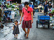 01 DECEMBER 2016 0 BANGKOK, THAILAND: A man and his daughter in the traditional market on Lan Luang Road in Bangkok. The market is on the site of one of the first western style cinemas in Bangkok. The movie theatre closed years ago and is still empty but the market fills the streets around the theatre.     PHOTO BY JACK KURTZ