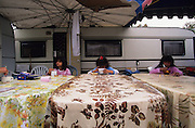 """Europe, France, Camargue, Saintes Maries de la Mer. Three young Gitan cousins have a late morning breakfast. The Gypsy festival """"le Pelerinage des Gitans aux Saintes Maries de la Mer"""" takes place every year in mid May. Gypsies arrive from all over Europe a few weeks before the main festival days, the 24th and 25th May.  The pilgrimmage is Catholic but many Gypsies, Manouche, Gitans, Roma come to see their patron 'Saint Sara' and for the festival atmosphere, the yearly gathering of friends, the music and dance. Gypsies are still regarded with much distrust and racism, they are not liked by the shopkeepers but are well treated by the gentry, especially the Baroncelli family who were instrumental in making this officially a Gypsy festival. One Hundred years ago the Gypsies were not allowed into the church, as it is they still have to camp outside the town."""