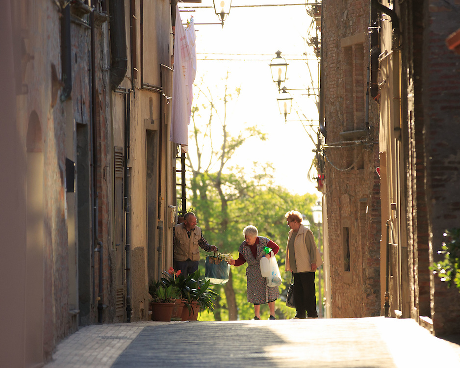 An Old lady and an old man chat flowers in Montaione village, Tuscany, Italy