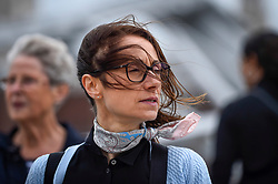 © Licensed to London News Pictures. 10/08/2019. LONDON, UK.  A woman crosses the Millennium Bridge during windy conditions.  Much of the UK forecast to be subject to strong winds for the weekend.  Photo credit: Stephen Chung/LNP