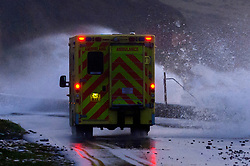 © Licensed to London News Pictures. 13/01/2020. Amroth, Carmarthenshire, Wales, UK. An ambulance negotiates the coast road between Amroth and Pendine as Storm Brendan hits the South West coastline of  Wales, UK. Photo credit: Graham M. Lawrence/LNP