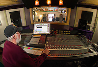 Franz Haase operates the control panel with Ryan Ordway at the mike at their recording studio for the Recording Coop in Gilford on Wednesday morning.  (Karen Bobotas/for the Laconia Daily Sun)