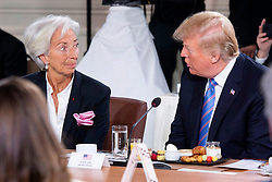 IMF Managing Director Christine Lagarde looks on as U.S. President Donald Trump takes his seat after arriving late for the G7 and Gender Equality Advisory Council Breakfast at the G7 leaders summit in La Malbaie, Que., on Saturday, June 9, 2018. Photo by Justin Tang/CP/ABACAPRESS.COM