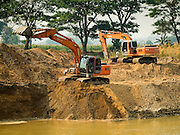 "01 APRIL 2016 - WANG NUEA, LAMPANG, THAILAND:   Workers make a temporary catchment called a  ""Kaem Ling"" (Monkey Cheek) in the Mae Wang (Wang River) in Wang Nuea. The river should be free flowing and waist deep at this time of year but is stagnant this year. The Kaem Ling project is an effort by the Thai government to keep some water in the riverbeds and canals. The Mae Wang flows into the Chao Phraya River and on to Bangkok and provides domestic and irrigation water for much of northern Thailand. The rainy season is not expected to start for at least two more months.    PHOTO BY JACK KURTZ"