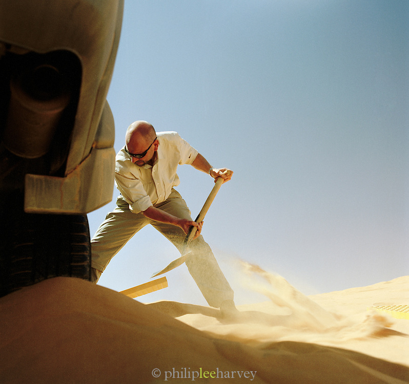 A man digs sand out from under a 4x4 vehicle that has lost traction in the sand of the Sahara desert, Libya