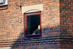 © Licensed to London News Pictures. 08/05/2018. OXFORD, UK.  A police officer stands in a window of a property in Paradise Square following an exchange of gunfire between a man and police yesterday and an armed siege overnight. Only a small cordon remains behind a row of terraced houses. A 24 year old man was arrested at 3am this morning on suspicion of attempted murder. Photo credit: Cliff Hide/LNP