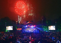© Licensed to London News Pictures. 24/08/2013. London, UK . The concert ended with a large firework display. The Torrential rain did not dampen the spirit of the audience who joined in with Jerusalem and Rule Britannia, despite very heavy rain. The Royal Choral Society together with the Royal Philharmonic Concert Orchestra, performs an evening of the choral classics in Heavy rain at Live by the Lake. The English Heritage concert season returns to Kenwood House in Hampstead, London, with Live by the Lake. The season includes Suede, a Choral Greats concert, Keane, an outdoor live screening of Singin' in the Rain featuring the Royal Philharmonic Concert Orchestra, Opera Alfresco and an evening of Gershwin. . Photo credit : Stephen Simpson/LNP