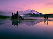 Purple dawn light enhances a sunrise reflection of South Sister peak in the quiet waters of Sparks Lake, Oregon.