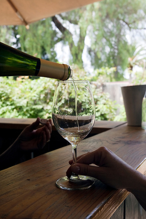Wine is poured into a glass at a wine tasting in Los Olivos, California.