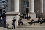 On the day that Chancellor of the Exchequer Rishi Sunak unveiled a £30bn package to boost the economy and get the country through the coronavirus outbreak, a lady wearing a surgical mask makes a call alongside others enjoying early Spring sunshine on the steps of Royal Exchange in the capital's financial district, as the Bank of England's governor Mark Carney cut the interest rate from 0.75% to 0.25%, on 11th March 2020, in the City of London, England.