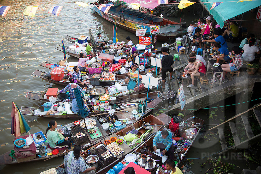 Food vendors moor their canoes along the canal bank of Amphawa floating market in Thailand, Southeast Asia