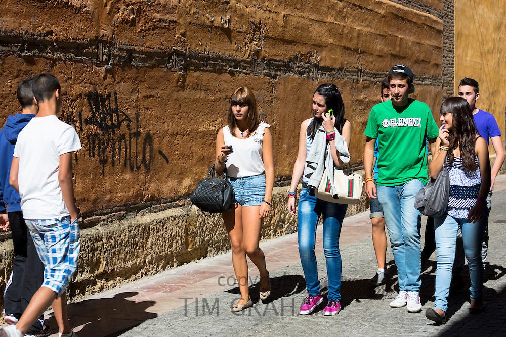 Young students strolling in Calle Sacramento in Leon, Castilla y Leon, Spain