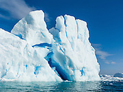 A blue iceberg juts from the Southern Ocean at Graham Land, in Antarctica.