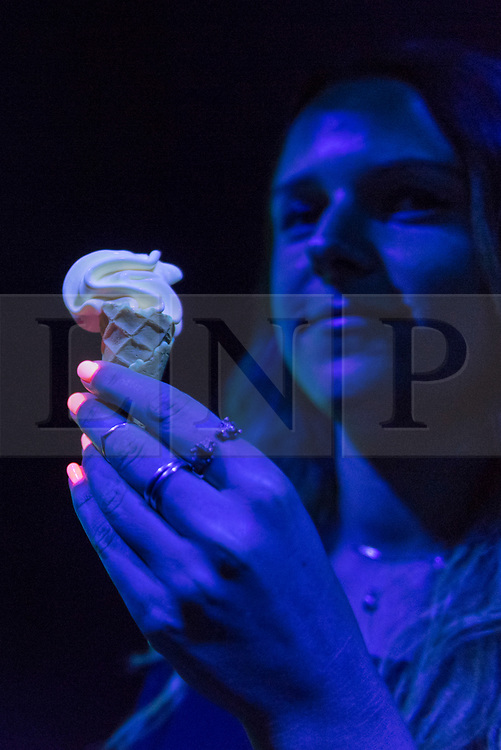 "© Licensed to London News Pictures. 03/07/2018. LONDON, UK. A staff member presents glow in the dark ice cream at a preview of ""SCOOP: A Wonderful Ice Cream World"", the first official exhibition of the British Museum of Food.  The exhibition presents items from the Robin and Caroline Weir Collection and explores the science and appeal of ice cream going back 400 years.  The exhibition takes place at the Gasholders near Granary Square in Kings Cross and runs 3 July to 30 September 2018.  Photo credit: Stephen Chung/LNP"