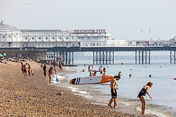 Licensed to London News Pictures. 06/09/2021. Brighton, UK. Swimmers cool off in the sea at Brighton Beach, East Sussex as weather forecaster predict a mini-heatwave for September this week with temperatures hitting over 29c tomorrow. Photo credit: Alex Lentati/LNP