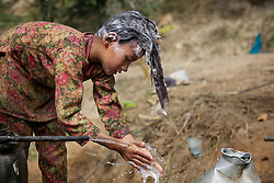 Durga and Niruta's oldest child Sumitra, 10, washes her hair outside the cow shed one afternoon. <br /> <br /> Niruta and Durga were married 9 years ago, when they were just 14 and 16 years old in the Kagati village of Nepal. The 2015 earthquakes devastated Nepal and left girls and women in an increasingly vulnerable position, leading experts to believe child marriage rates will increase over the coming years.