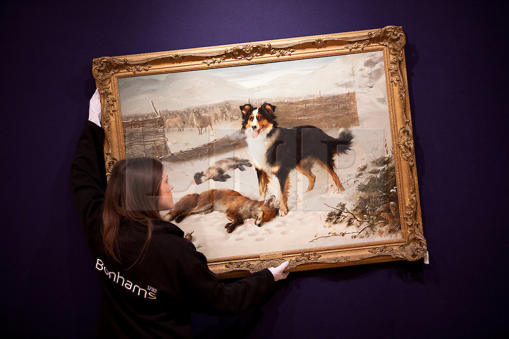 © Licensed to London News Pictures. 15/01/2013. London, UK. A Bonhams employee adjusts a snowy scene in the form of a watercolour by British artist Walter Hunt entitled 'Retribution' (1884) (Est. GB£7,000-10,000), at an auction press view held today (15/01/13) at Bonhams in New Oxford Street, London. The auction, '19th Century Paintings, Drawings and Watercolours', will take place on the 23rd of January at Bonhams' 101 New Bond Street Premisses. Photo credit: Matt Cetti-Roberts/LNP