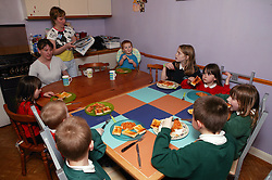 Two mothers in the kitchen with their children at mealtime,
