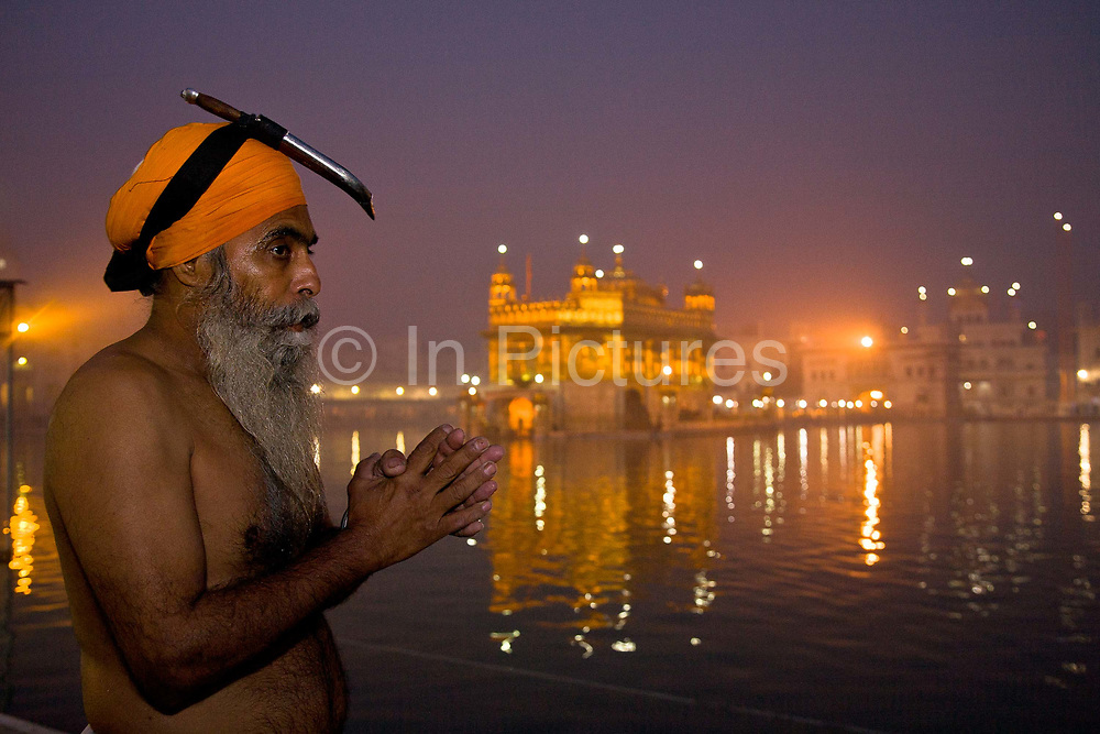 A Sikh devotee / pilgrim in prayer shortly after having bathed in the amritsagar, the water surrounding the Golden Temple in Amritsar, Punjab, India