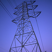 Vertical shot of power lines and tower against dark blue, dusk sky with moon.