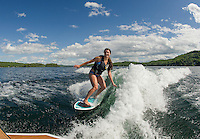 Julia Cantin rides the wave off her family's boat during an evening of wake surfing on Lake Winnisquam.  (Karen Bobotas/for the Laconia Daily Sun)