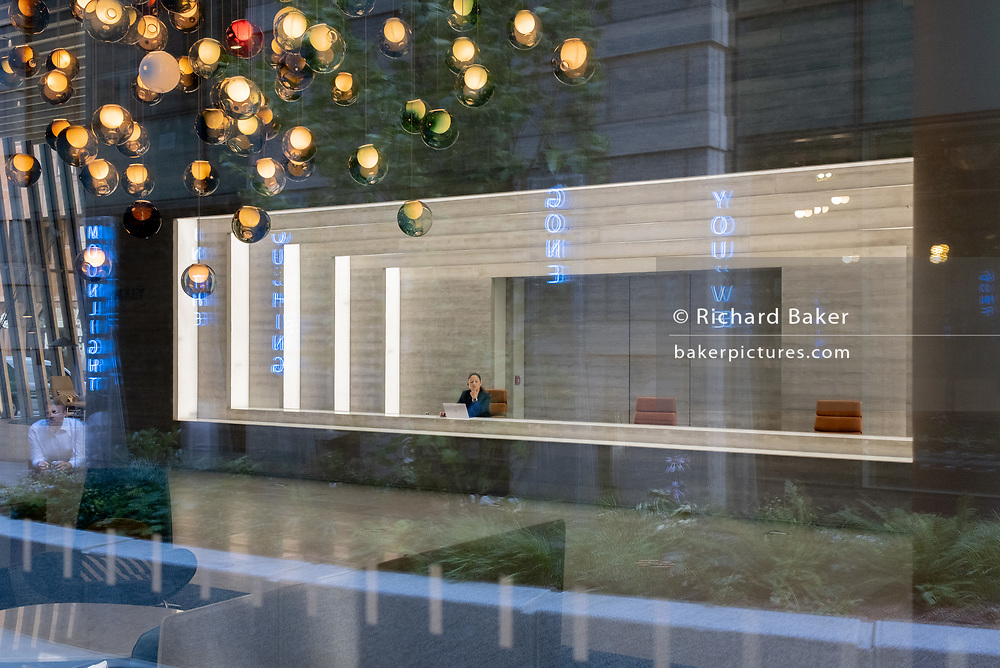 A receptionist sits in the foyer of corporate office space in the City of London, on 29th July 2020, in London, England.