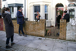 © Licensed to London News Pictures. 25/12/2020. London, UK. Friends and neighbours celebrating Christmas in front garden in north London. The government announced that people in Tier 4 areas, including London, cannot mix with any other households over Christmas, but support bubble can meet outside their home. Photo credit: Dinendra Haria/LNP