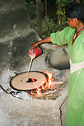 Africa, Ethiopia, Lalibela, Woman cooking Injera (pancake like bread) on a mogogo over a fire