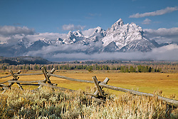 """The first snow on the Grand Tetons in Grand Teton National Park. A buckrail rail fence accents the western heritage of the Jackson Hole Valley.<br /> <br /> For production prints or stock photos click the Purchase Print/License Photo Button in upper Right; for Fine Art """"Custom Prints"""" contact Daryl - 208-709-3250 or dh@greater-yellowstone.com"""
