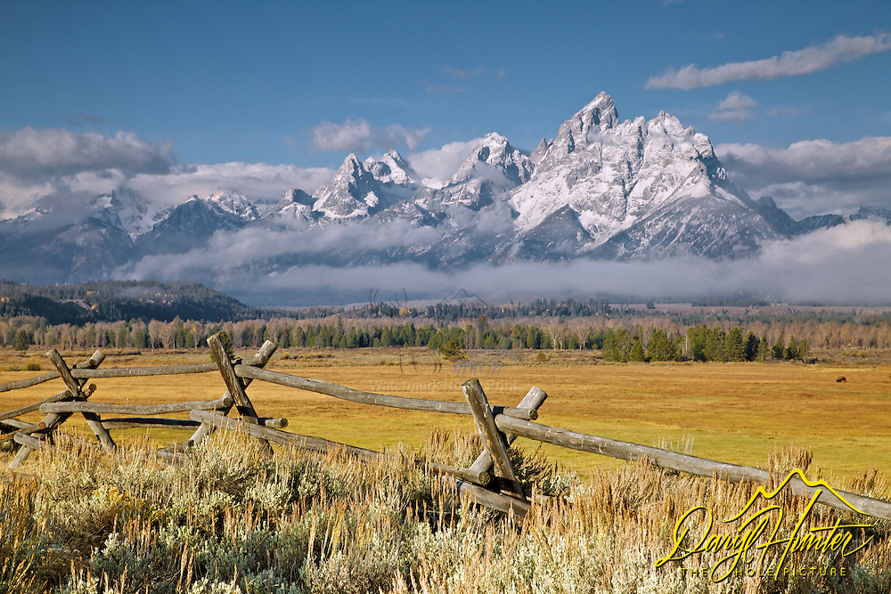 The first snow on the Grand Tetons in Grand Teton National Park. A buckrail rail fence accents the western heritage of the Jackson Hole Valley.<br />