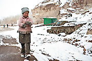 A young girl walks by the rusting hulk of a Soviet tank in Bamiyan Town.
