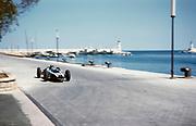Forumla One motor racing Monaco Grand Prix 1961, Bruce McLaren in Cooper-Climax approaching tobacconist kiosk