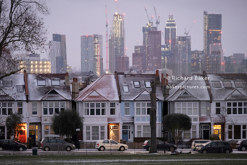 Snow-covered roofs and the glowing lights in the porches of south London Edwardian homes and residential high-rise towers under construction, on 8th February 2021, in London, England.