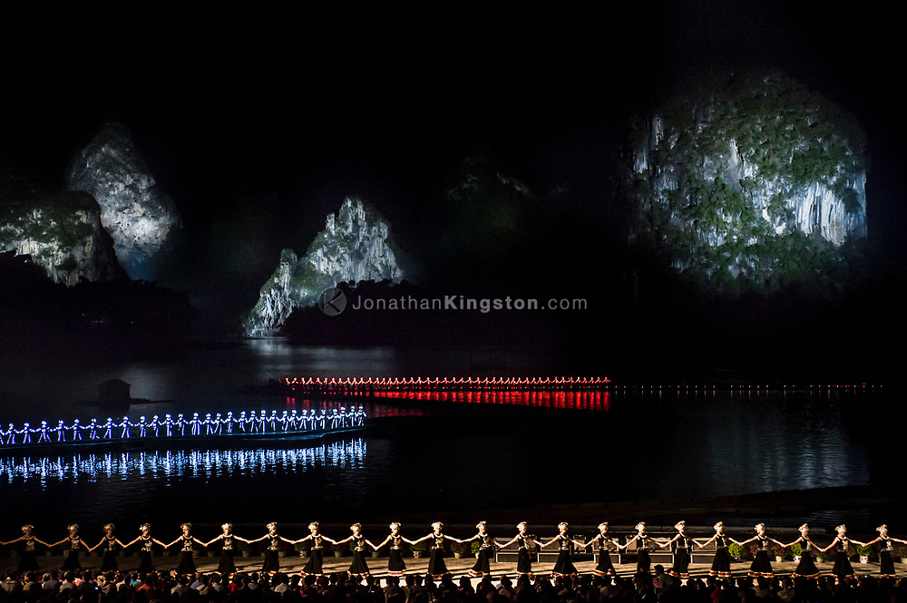 Performers holding hands in lit blue and red body suits illuminate the night during an outdoor theater performance of the Liu Sanjie light show titled The Impression, at an outdoor theater at night in Yangshuo, China.