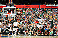 29 MAR 2015: Marvin Clark Jr. (0) of Michigan State University shoots a three pointer over Mangok Mathiang (12) of the University of Louisville during the 2015 NCAA Men's Basketball Tournament held at the Carrier Dome in Syracuse, NY. Michigan State defeated Louisville 76-70 to advance. Brett Wilhelm/NCAA Photos