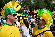 London, UK. Thursday 12th June 2014. Two friends wearing mohawk wigs. Brazilians gather for the Brazil Day celebrations in Trafalgar Sq. A gathering to celebrate the beginning of the Brazil 2014 FIFA World Cup. Revellers sing and dance and play football games and all in the yellow green and blue of the Brazilian flag.