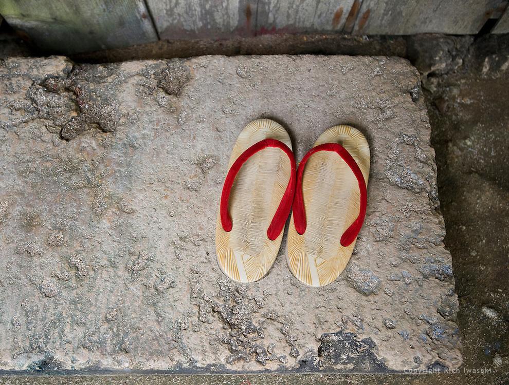 Slippers sit outside of building entrance at Ryuku Mura, Onna Village, Okinawa, Japan