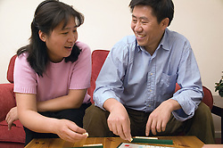 Couple playing a game of scrabble together at home,
